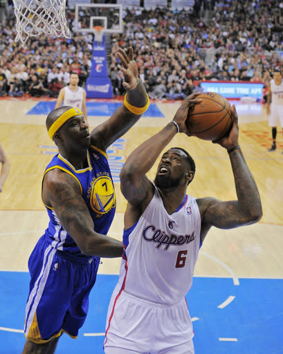 Los Angeles Clippers center DeAndre Jordan, right, puts up a shot as Golden State Warriors center Jermaine O'Neal defends during the second half in Game 5 of an opening-round NBA basketball playoff series, Tuesday, April 29, 2014, in Los Angeles. The Clippers won 113-103. (AP Photo)