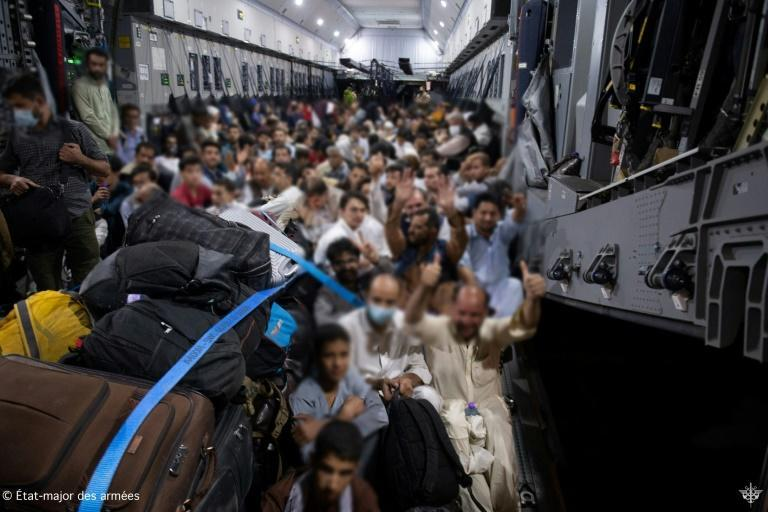 People board a French military transport aircraft in Kabul to fly to the air base of Al Dhafra near Abu Dhabi, and then to France on August 26, 2021 following the Taliban takeover (AFP/-)