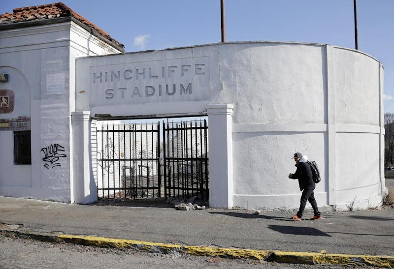 A man walks past an entrance to Hinchliffe Stadium in Paterson, N.J. on Thursday, March 14, 2013. Hinchliffe, built as a public works project municipal stadium in 1932, now sits in disuse, with trees growing in the graffiti covered stands and a deteriorated artificial turf surface. The once-grand Art Deco stadium earned designation in March as a national landmark - less than two years after the nearby Great Falls, a powerful 77-foot waterfall that helped fuel the Industrial Revolution, became a national park. (AP Photo/Mel Evans)