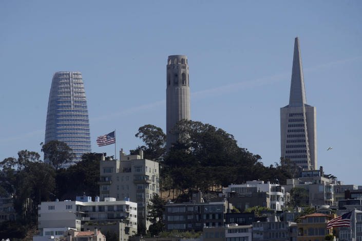 FILE - In this June 18, 2020, file photo, Coit Tower, center, is seen between Salesforce Tower, left, and the Transamerica Pyramid from Pier 39 in San Francisco. The Transamerica Pyramid, one of San Francisco's iconic buildings, has sold for $650 million, eight months after a sales agreement was reached. (AP Photo/Jeff Chiu, File)