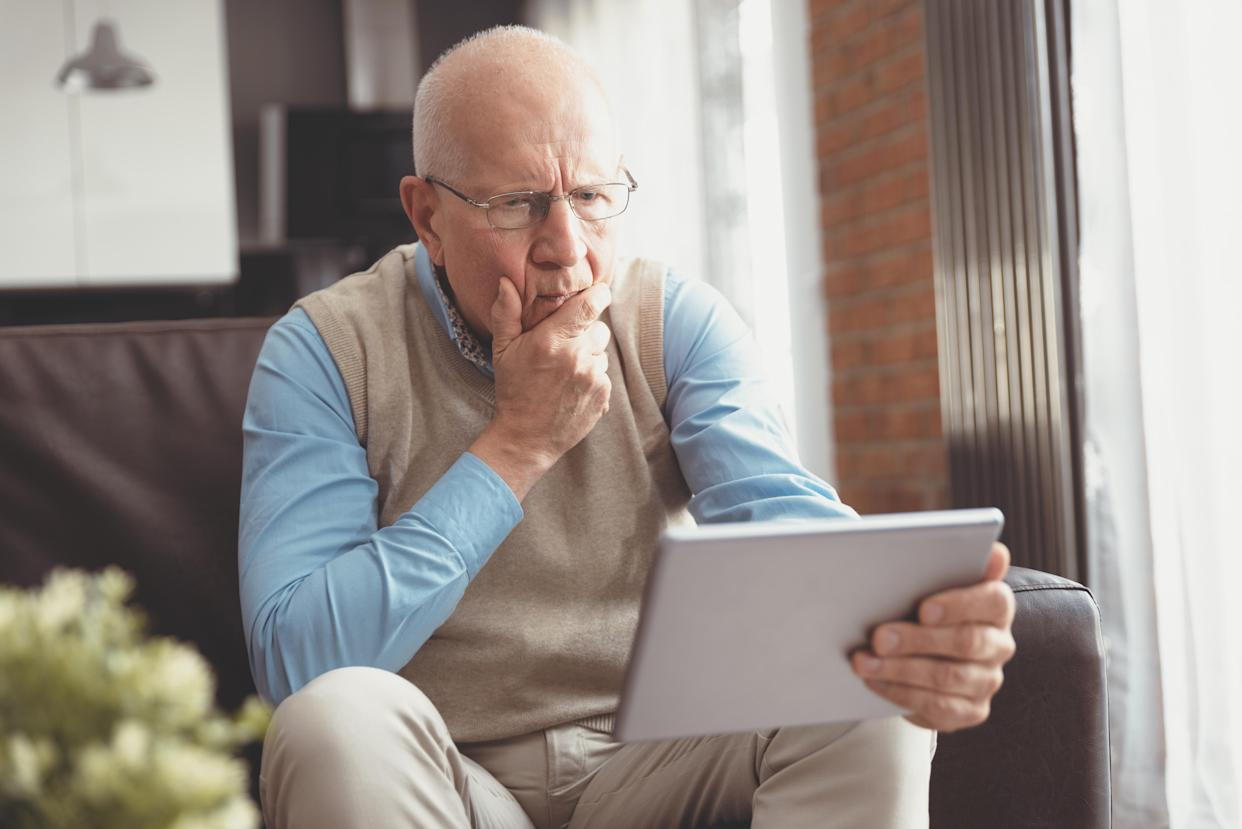 Senior man surprised using a digital tablet while sitting on couch at home