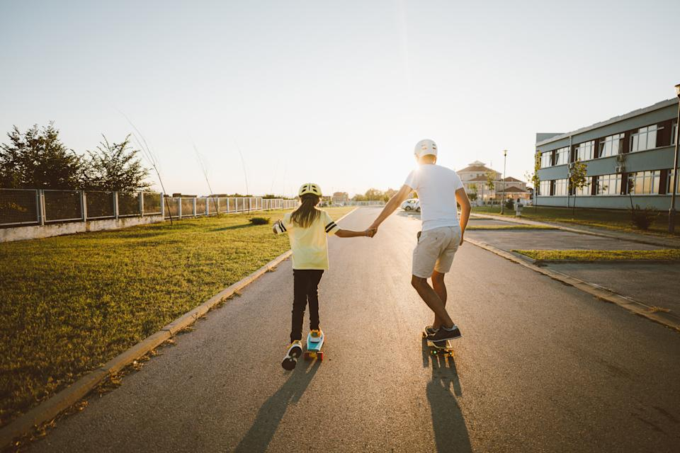 Photo of father and daughter skateboarding outdoors; spending time together and enjoying the beautiful sunny day.