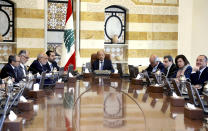 In this photo released by Lebanon's official government photographer Dalati Nohra, Lebanese President Michel Aoun, center, heads the cabinet meeting, at the presidential palace, in Baabda, east of Beirut, Lebanon, Monday, Oct. 21, 2019. Protesters closed major roads around Lebanon ahead of an emergency cabinet meeting on Monday, as politicians scrambled to put together a rescue plan for the country's crumbling economy and stem five days of mass anti-government protests. (Dalati Nohra via AP)