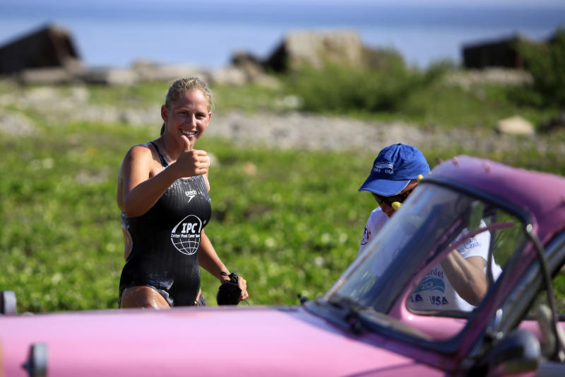 Australian swimmer Chloe McCardel flashes a thumbs up at people gathered to watch her begin her swim to Florida from Havana, Cuba, Wednesday, June 12, 2013. The Australian endurance athlete is hoping to become the first person to swim from Havana to Florida without a protective shark cage. McCardel says she expects to spend about 60 hours in the sea before reaching the Florida Keys, a little more than 100 miles to the northeast. (AP Photo/Franklin Reyes)
