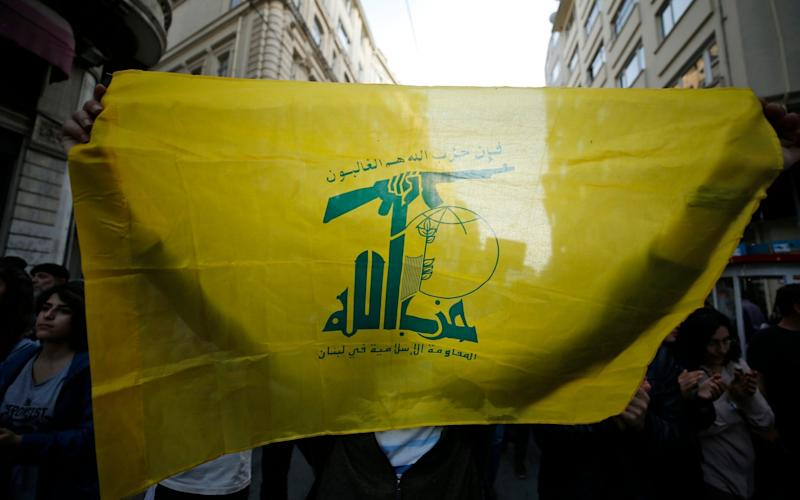 A protester holds a flag of Lebanon's Hezbollah militant group - Emrah Gurel