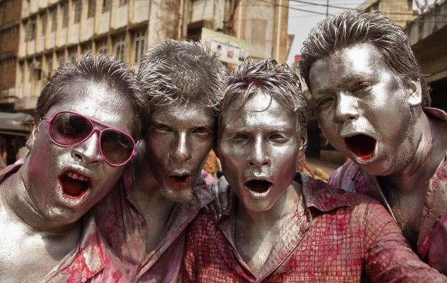 Men with their faces painted in silver pose as they celebrate Holi in the northeastern Indian city of Guwahati March 17, 2014. Holi, also known as the Festival of Colours, heralds the beginning of spring and is celebrated all over India. REUTERS/Utpal Baruah (INDIA - Tags: SOCIETY RELIGION)