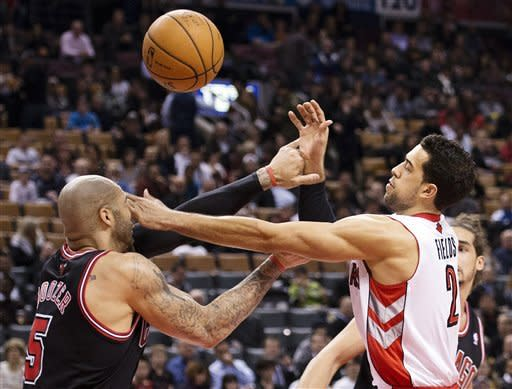 Toronto Raptors forward Landry Fields, right, battles for a loose ball against Chicago Bulls forward Carlos Boozer during the first half of their NBA basketball game, Wednesday, Jan. 16, 2013, in Toronto. (AP Photo/The Canadian Press, Nathan Denette)