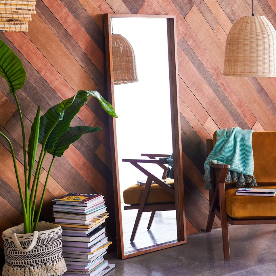 <p>Add a full length mirror like the <span>Wood Rectangle Leaner Mirror Brown 24 inch x 65 inch by Drew Barrymore Flower Home</span> ($125, originally $150) to open up your room.</p>