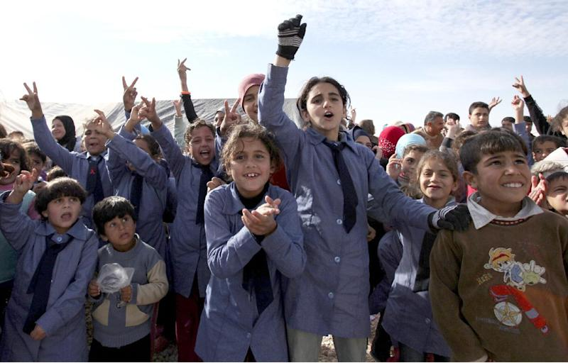 """Syrian refugee students wave to welcome United Nations Secretary-General Ban Ki-moon, unseen, to Zaatari Syrian refugee camp, in Mafraq, Jordan, near the Syrian border, Saturday, Dec. 7, 2012. U.N. Secretary-General Ban Ki-Moon on Friday called on the Syrian government to """"stop the violence in the name of humanity"""", during a visit to the Zaatari refugee camp in Jordan, close to the Syrian border. (AP Photo/Mohammad Hannon)"""