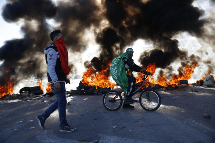 Palestinian wrapped in Hamas flag rides a bike during clashes with Israeli troops at the Hawara checkpoint, south of the West Bank city of Nablus, Friday, Dec. 14, 2018. (AP Photo/Majdi Mohammed)