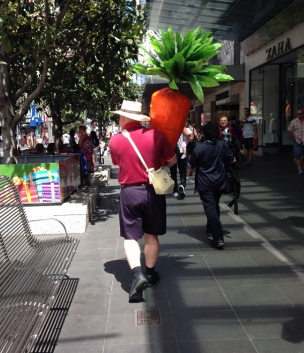 """""""Carrot man"""" Nathan walking in Melbourne with his giant vegetable."""
