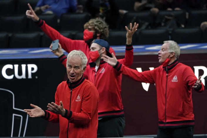 Team World's captain John McEnroe, bottom left, vice captain Patrick McEnroe, far right, and teammates applaud a point by Felix Auger-Aliassime, of Canada, during his match against Team Europe's Matteo Berrettini, of Italy, at Laver Cup tennis, Friday, Sept. 24, 2021, in Boston. (AP Photo/Elise Amendola)