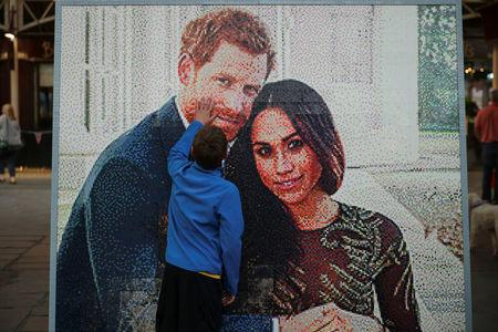 A boy touches a LEGO brick mosaic of Britain's Prince Harry and Meghan Markle in Windsor, Britain, May 18, 2018. REUTERS/Marko Djurica
