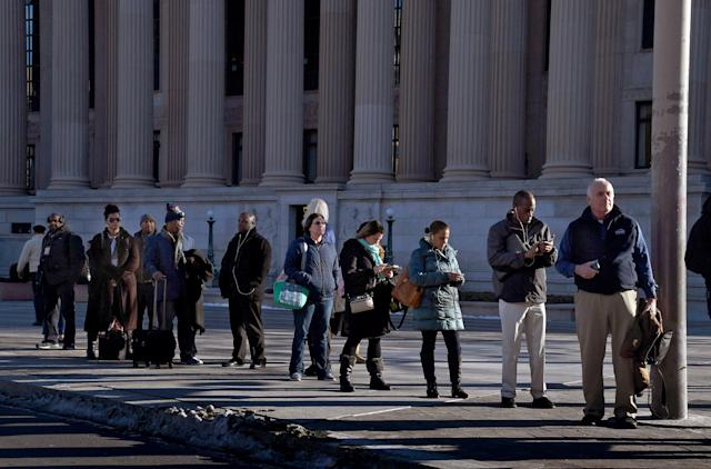 <p>Workers wait for a commuter bus in front of the Archives building on Pennsylvania Ave. in NW Washington. (Photo: Michael S. Williamson/The Washington Post via Getty Images) </p>