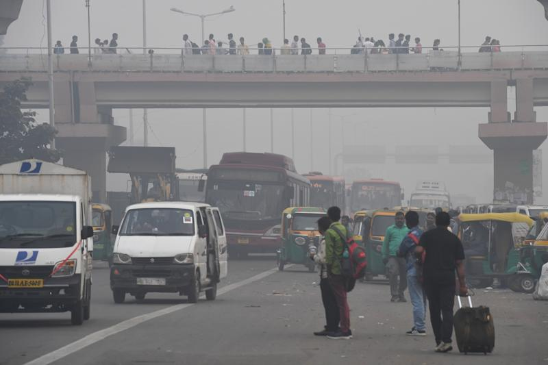 People make their way on a street in smoggy conditions in New Delhi on Nov. 4, 2019. (Photo: Prakash Singh/AFP via Getty Images)