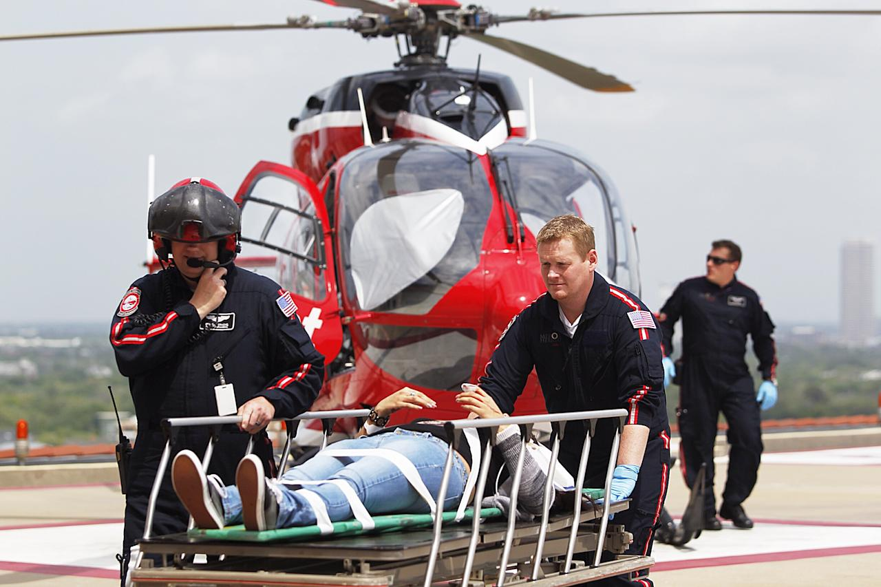 Life Flight personnel rush a victim wounded in a stabbing attack on the Lone Star community college system's Cypress, Texas campus into Memorial Hermann Hospital Tuesday, April 9, 2013, in Houston. The Harris County Sheriff's department confirmed at least 11 people wounded and that authorities have one suspect in custody. (AP Photo/Houston Chronicle, Johnny Hanson)