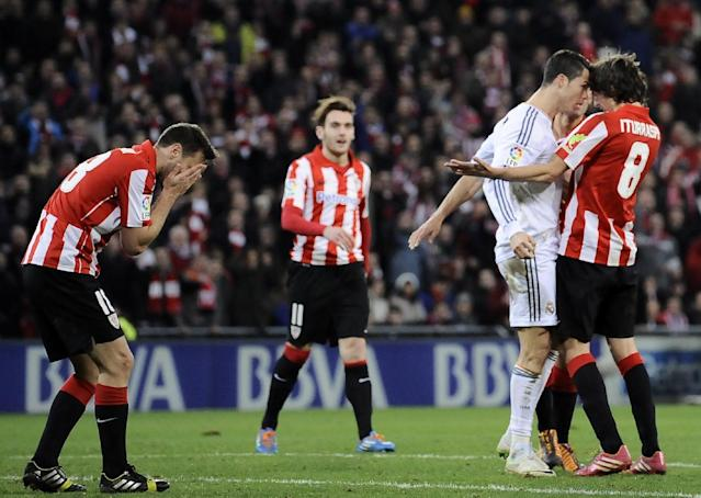 Real Madrid's Cristiano Ronaldo of Portugal, second right, discusses with Athletic Bilbao's Ander Iturraspe, right, after swiping his hand across the face of Athletic Bilbao's Carlos Gurpegi, left, following a shove from his opponent, during their Spanish League soccer match against Athletic Bilbao, at San Mames stadium in Bilbao, Spain, Sunday, Feb. 2, 2014. (AP Photo/Alvaro Barrientos)