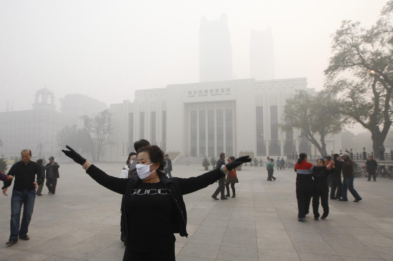 A Chinese woman wears a mask as she takes part in communal dancing during a day of heavy pollution in Harbin in northeast China's Heilongjiang province Monday Oct. 21, 2013. Visibility shrank to less than half a football field and small-particle pollution soared to a record 40 times higher than an international safety standard in the northern Chinese city as the region entered its high-smog season. (AP Photo) CHINA OUT