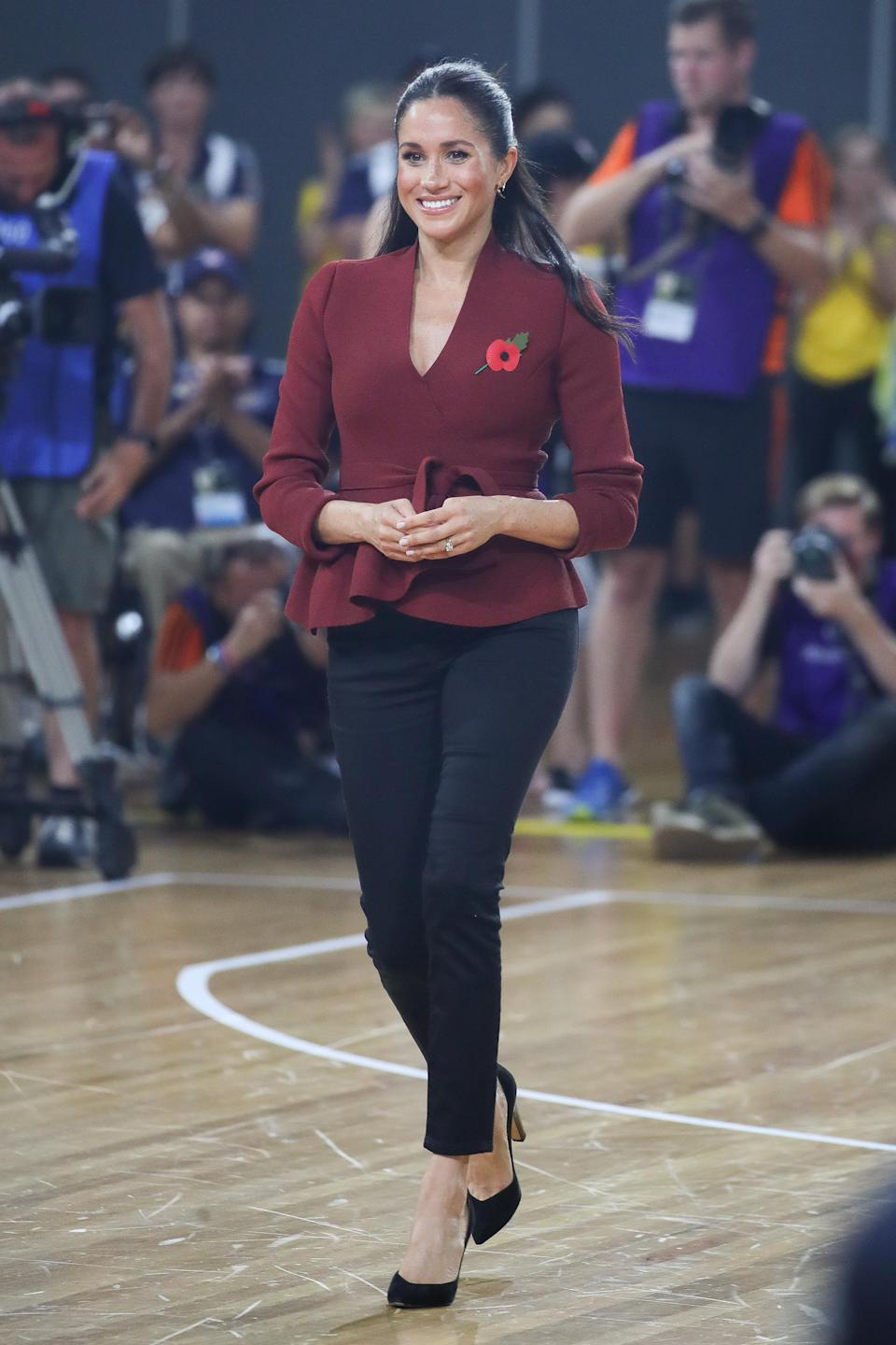 """<p>For the 2018 Invictus Games wheelchair basketball finale, Meghan wore a £303 plum-hued jacket by Aussie label <a rel=""""nofollow noopener"""" href=""""https://us.scanlantheodore.com/collections/w18-rwt/products/crepeknitwrapjacketgarnet"""" target=""""_blank"""" data-ylk=""""slk:Scanlan Theodore"""" class=""""link rapid-noclick-resp"""">Scanlan Theodore</a> with skinny jeans. <em>[Photo: Getty]</em> </p>"""