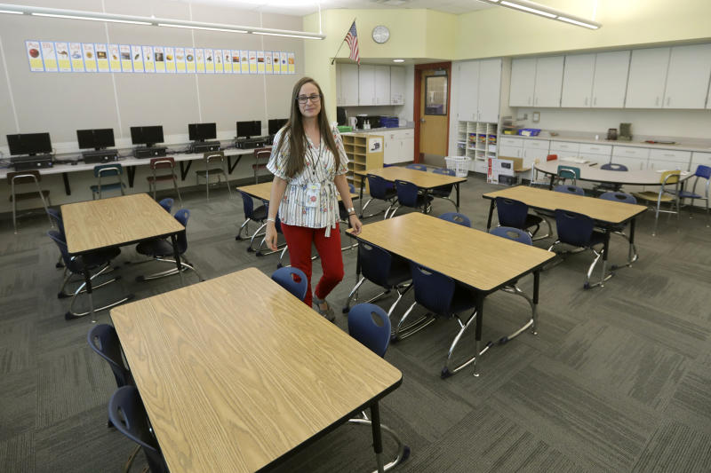 """First-grade teacher Hillary Madrigal is photographed in her classroom Thursday, Aug. 22, 2019, in Salt Lake City. Across the country, teachers and school districts alike are grappling with the latest political and economic realities of educator pay. Madrigal jumped to the nearby school district last year, lured by higher salaries that would allow her to quit her second job as a housekeeper and buy a new car. """"I have a college degree. I felt I could make a difference in people's lives as a teacher but to pay my bills ... I had to do people's laundry,"""" said Madrigal, who now works for the Salt Lake City School District. (AP Photo/Rick Bowmer)"""