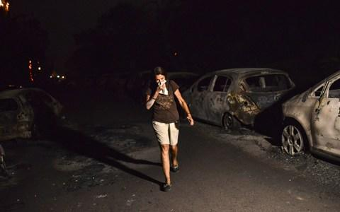 A woman walks in front of burnt cars at the village of Mati during a wildfire near Athens - Credit: AFP
