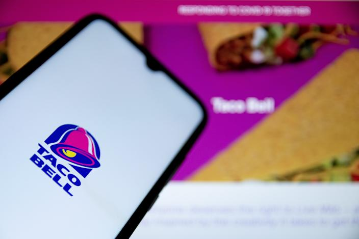 GREECE - 2021/05/07: In this photo illustration a Taco Bell logo seen displayed on a smartphone screen with Taco Bell website in the background. (Photo Illustration by Nikolas Joao Kokovlis/SOPA Images/LightRocket via Getty Images)