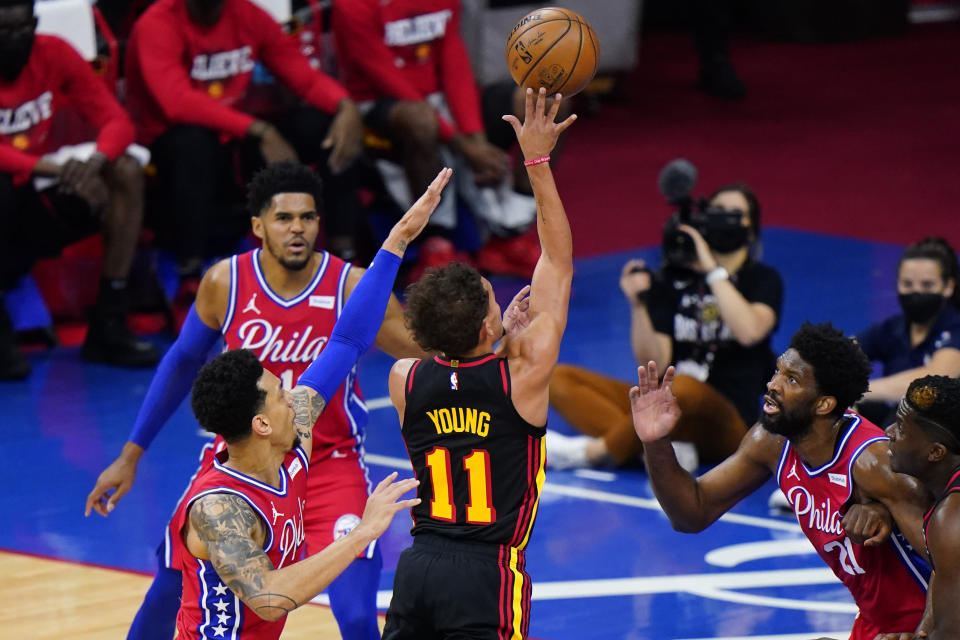 Atlanta Hawks' Trae Young, center, goes up for a shot against Philadelphia 76ers' Danny Green, from left, Tobias Harris and Joel Embiid during Game 1 of a second-round NBA basketball playoff series against the Philadelphia 76ers, Sunday, June 6, 2021, in Philadelphia. Young became the second player in NBA history to score 30 points in each of his first four career playoff road games. The latest came in Atlanta's surprising Game 1 victory in Philadelphia. (AP Photo/Matt Slocum)