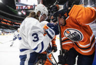Edmonton Oilers' Patrick Russell (52) and Toronto Maple Leafs' Justin Holl (3) battle for the puck during the second period of an NHL game in Edmonton, Alberta, on Saturday, Feb. 27, 2021. (Jason Franson/The Canadian Press via AP)