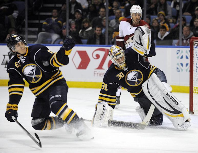 Buffalo Sabres' Tyler Ennis (63) and Ryan Miller (30) each get a glove up as Phoenix Coyotes' Mike Ribeiro (63) watches the rebound during the second period of an NHL hockey game in Buffalo, N.Y., Monday, Dec. 23, 2013. (AP Photo/Gary Wiepert)