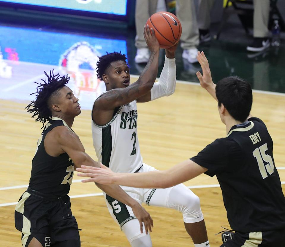 Michigan State Spartans guard Rocket Watts scores against Purdue Boilermakers guard Jaden Ivey and  center Zach Edey during the first half at Breslin Center in East Lansing, Friday, Jan. 8, 2021.