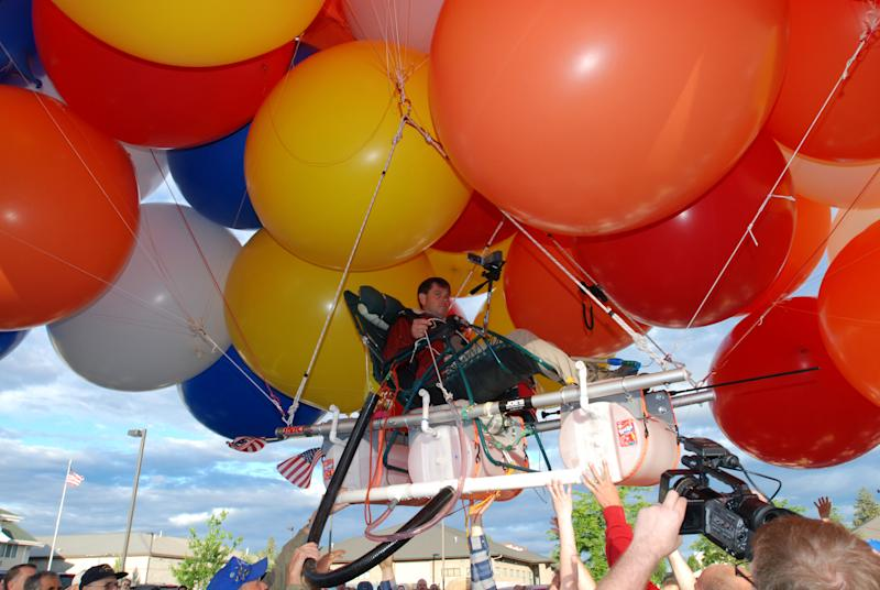 "FILE - This July 5, 2008 file photo shows Kent Couch lifting off from his gas station in Bend, Ore., riding a lawn chair rigged with more than 150 giant party balloons for a flight that ended 235 miles away in an Idaho farm field. Oregon's ""lawn-chair balloonist"" has put off his flight in Iraq until next year. Couch had planned another balloon flight Tuesday, Nov. 15, 2011 in Baghdad along with Iraqi daredevil Fareed Lafta. But a statement Monday from spokesman Mark Knowles says the two have delayed the flight until March to accommodate a number of groups that want to use it to raise awareness of the plight of Iraqi orphans. (AP Photo/Jeff Barnard, File)"