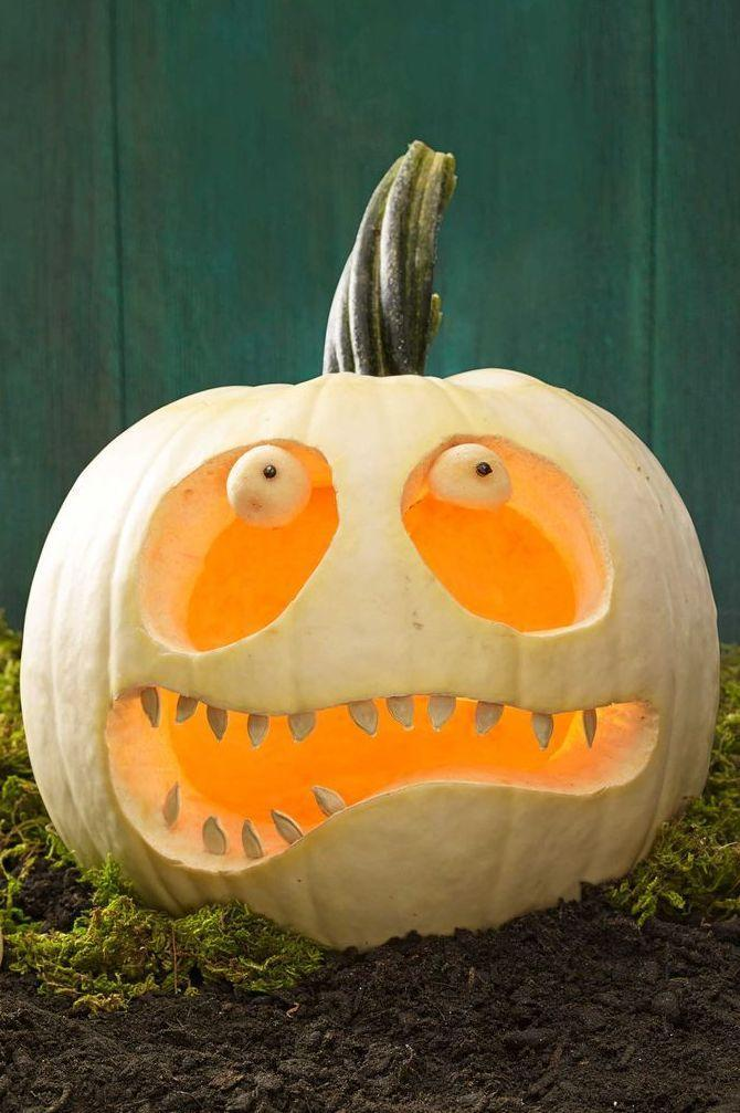 <p>Oversized eyes make this ghoulish zombie pumpkin truly eerie. <strong><br></strong></p><p><strong>Make the Zombie Pumpkin:</strong> Using a craft knife, cut a hole in the top of the pumpkin and hollow out the inside. Scrape away any extra flesh with a spoon. Rinse a handful of the seeds (about 16 or so), pat dry and set aside. <br></p><p>Lightly draw two large ovals for eyes (position them slightly tilted towards each other for a sweeter, less scary look) and a wide, slightly lopsided mouth. Carve out with a craft knife; save scraps. Use the melon baller to carve out two round eyeballs from the fleshy side of reserved pumpkin scraps. Spear each eyeball with a toothpick and attach to the tops of the eye cutouts. Gently press a peppercorn into the center of each to create pupils. Press the cleaned seeds directly into the mouth, positioning them in different directions. </p>