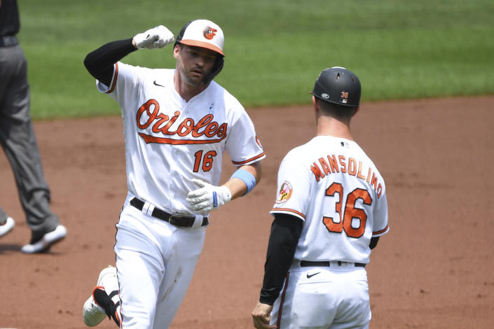 Baltimore Orioles Trey Mancini, left, fist bumps third base coach Tony Mansolino, right, after hitting a first inning home run against Toronto Blue Jays starting pitcher Hyun Jin Ryu during a baseball game, Sunday, June 20, 2021, in Baltimore. (AP Photo/Terrance Williams)