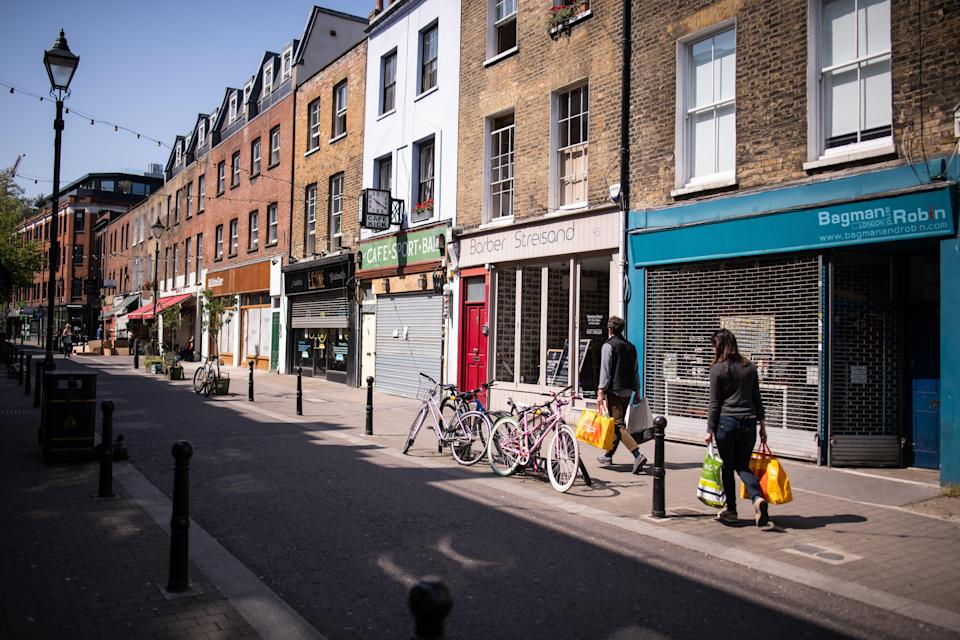 <p>A man and woman carry their shopping down the usually busy Exmouth Market in London</p> (Getty)