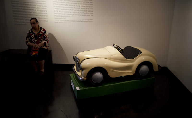 "A visitor sits near a toy pedal car of the ""Childhood and Peronism, the toys of the Eva Perón Foundation"" exhibit at the Evita Museum in Buenos Aires, Argentina, Wednesday, April 17, 2019. To mark the 100th anniversary of the birth of Argentina's so-called ""champion of the poor"" on May 7, 1919, the Evita Museum in Buenos Aires has inaugurated the exhibit, which displays several dozen of the toys distributed by the party on Christmas Day and the holiday of Epiphany between 1948 and 1955. (AP Photo/Natacha Pisarenko)"