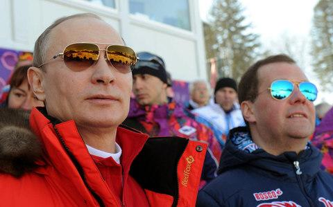 Vladimir Putin and Russian Premier Dmitry Medvedev watch the men's 4x10 km cross-country relay at the 2014 Winter Olympics in Krasnaya Polyana, Russia - Credit: AP