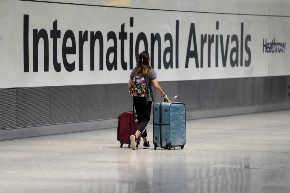 A passenger arrives from a flight at Terminal 5 of Heathrow Airport in London, Monday, Aug. 2, 2021. Travelers fully vaccinated against coronavirus from the United States and much of Europe were able to enter Britain without quarantining starting today, a move welcomed by Britain's ailing travel industry. (AP Photo/Matt Dunham)