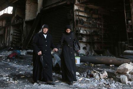 Women walk past damaged shop as they flee towards safer parts of Manbij city, in Aleppo Governorate, Syria, August 10, 2016. REUTERS/Rodi Said