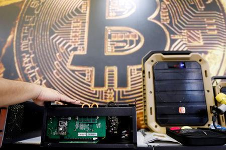 FILE PHOTO: A cryptocurrency mining computer is seen in front of bitcoin logo during the annual Computex computer exhibition in Taipei