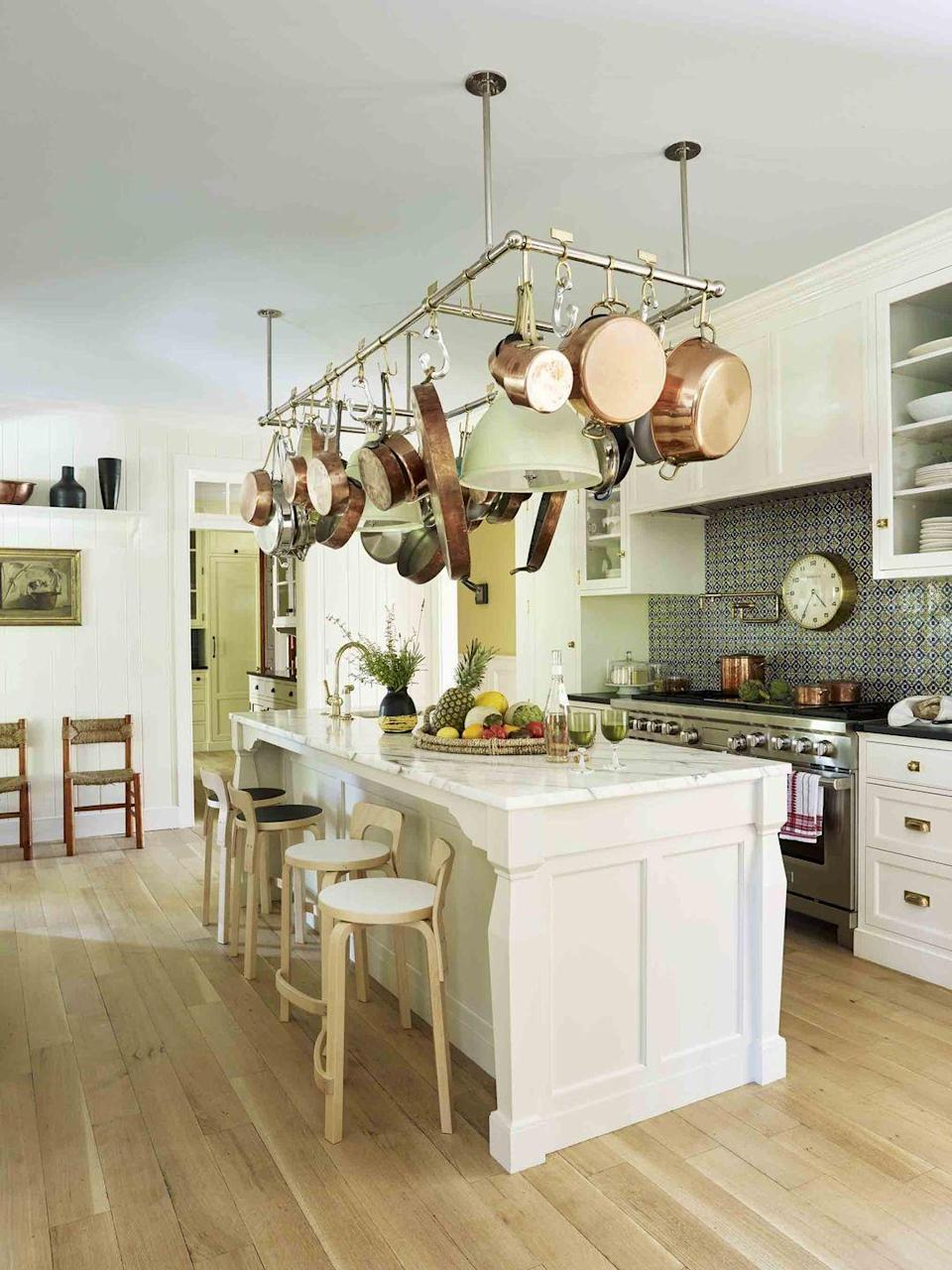 "<p>We love the French provincial look of using hanging storage for your best—and most frequently used—pots and pans. Designer <a href=""http://davidnettodesign.com/"" rel=""nofollow noopener"" target=""_blank"" data-ylk=""slk:David Netto'"" class=""link rapid-noclick-resp"">David Netto'</a>s use of added lighting ensures this hanging storage piece can be one giant light fixture if you decide to give your cookware another home, but it offers a bit of Old-World charm to the kitchen with very low lift. </p>"