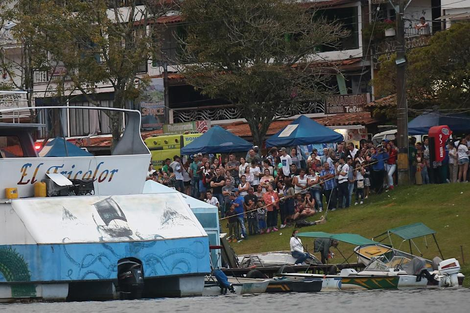 <p>Onlookers watch rescue efforts after the tourist boat Almirante sank in the Reservoir of Penol in Guatape municipality in Antioquia on June 25, 2017. (Joaquin Sarmiento/AFP/Getty Images) </p>