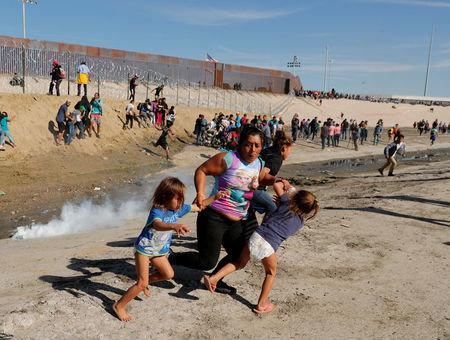 Maria Meza, a 40-year-old woman from Honduras traveling as part of a caravan of thousands from Central America to the United States, runs away from tear gas with her 5-year-old twin daughters Saira Mejia Meza and Cheili Mejia Meza. (Reuters)