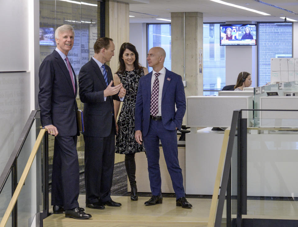 WASHINGTON, DC - JANUARY 28: Owner Jeff Bezos, right, with wife, MacKenzie, tours the newsroom with Publisher Fred Ryan, left, and TBA, second left, after dedication ceremonies for the new Washington Post offices on January, 28, 2016 in Washington, DC. (Photo by Bill O'Leary/The Washington Post via Getty Images)