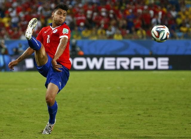 Chile's Gonzalo Jara lunges for the ball during their 2014 World Cup Group B soccer match against Australia at the Pantanal arena in Cuiaba June 13, 2014. REUTERS/Paul Hanna (BRAZIL - Tags: SPORT SOCCER WORLD CUP)