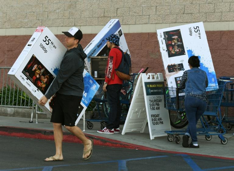 Shoppers with their arms full walk to their cars during the Black Friday sales at a Best Buy store in Culver City