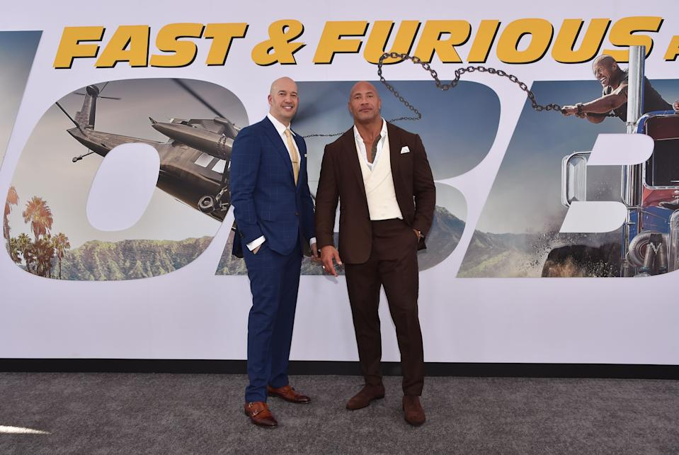 """US actor Dwayne Johnson (R) and producer Hiram Garcia (L) arrive for the World premiere of  """"Fast & Furious presents Hobbs & Shaw,"""" at the Dolby Theatre in Hollywood, California, July 13, 2019. (Photo by Chris Delmas / AFP)        (Photo credit should read CHRIS DELMAS/AFP via Getty Images)"""