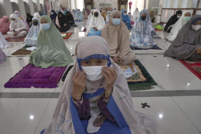 Muslims wearing face masks to curb the spread of coronavirus attend during an Eid al-Adha prayer at Zona Madina mosque in Bogor, Indonesia, Tuesday, July 20, 2021. Muslims across Indonesia marked a grim Eid al-Adha festival for a second year Tuesday as the country struggles to cope with a devastating new wave of coronavirus cases and the government has banned large gatherings and toughened travel restrictions. (AP Photo/Tatan Syuflana)