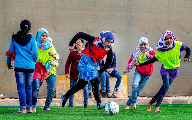 Girls playing football at on the Arsenal-funded pitch at Zaatari refugee camp - Pim Ras/Save the Children