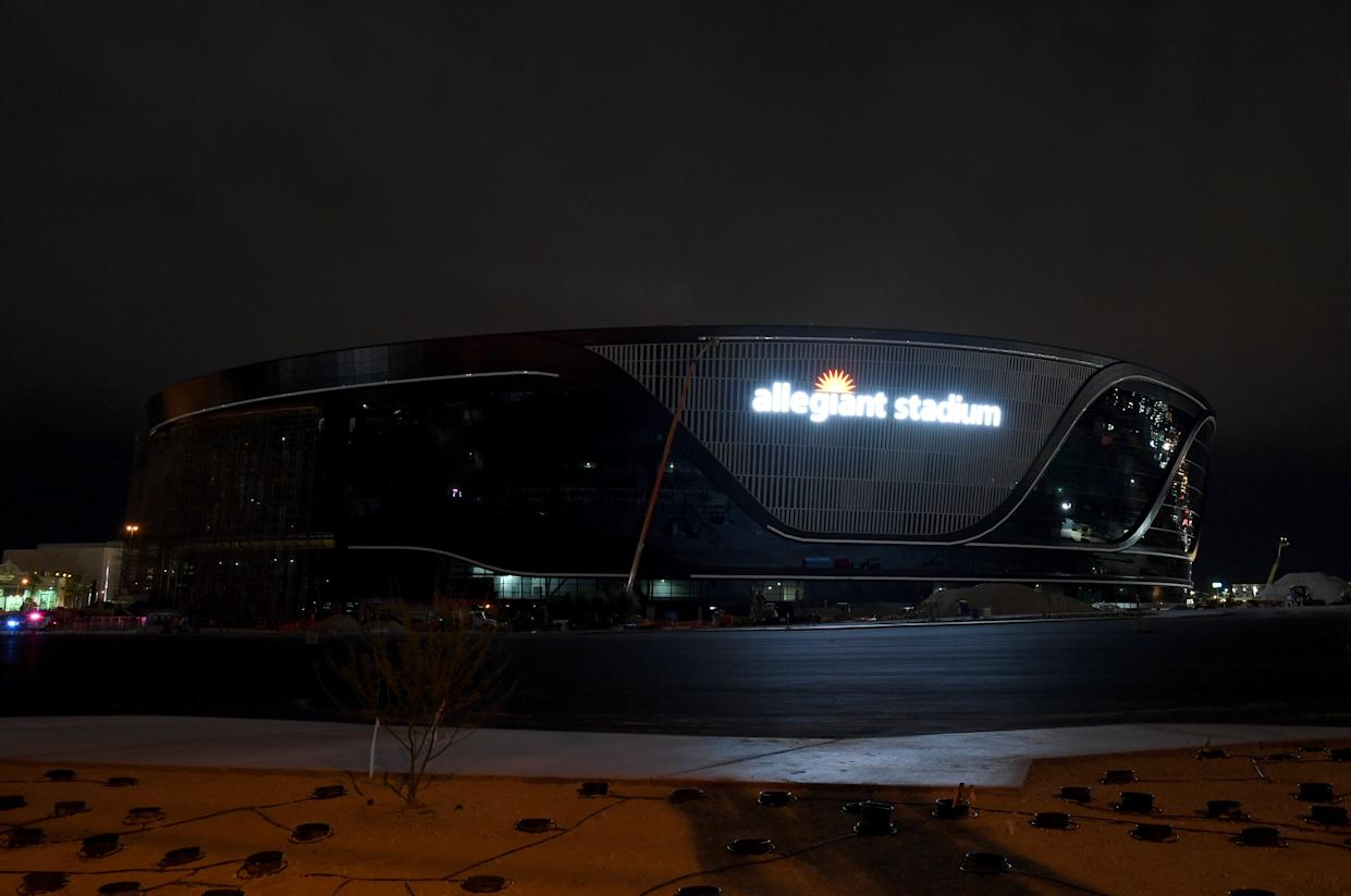 LAS VEGAS, NEVADA - APRIL 09:  Workers test the lighting on an exterior sign at Allegiant Stadium for the first time as construction continues on the USD 2 billion, glass-domed future home of the Las Vegas Raiders on April 9, 2020 in Las Vegas, Nevada. The Raiders and the UNLV Rebels football teams are scheduled to begin play at the 65,000-seat facility in their 2020 seasons.  (Photo by Ethan Miller/Getty Images)