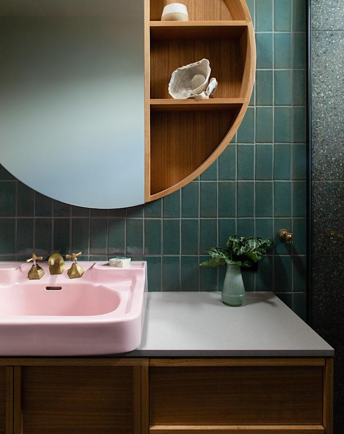 """AFTER: Megan reused the original bathroom's pink sink in the primary suite upstairs. Along with the primary bedroom and bathroom, there's a study—Megan calls it the """"parents' zone."""""""